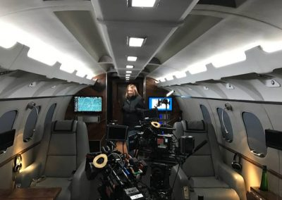 New private jet interior with filming equiment and woman